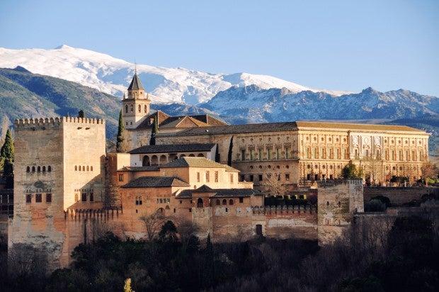 Atemberaubendes Panorama: Die weltberühmte Alhambra in Granada vor der imposanten Landschaft der Sierra Nevada.